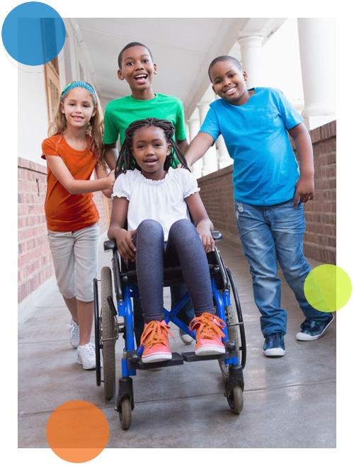 happy girl in a wheelchair surrounded by friends